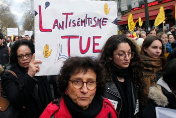 "A woman holding a sign reading ""The anti-Semitism kills,"" as she attends a silent march to honor 85-year-old Holocaust survivor Mireille Knoll, who was murdered in Paris in March 2018."