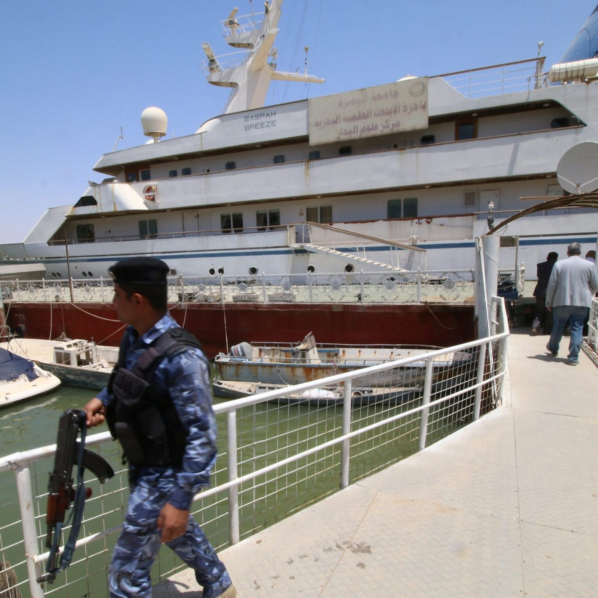 """An Iraqi policeman walks past the yacht called """"Basrah Breeze"""", once owned by former Iraqi president Saddam Hussein, who was toppled in a U.S.-led invasion in 2003, in the southern port of Basra, Iraq May 14, 2018."""