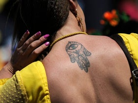 A pilgrim sporting a Hamsa hand tattoo on her back walks during her pilgrimage to the village of El Rocio, in Sanlucar de Barrameda on May 16, 2018.