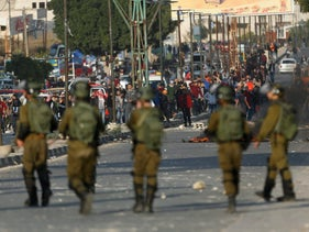 Palestinians clash with Israeli troops in Nablus following a protest against U.S. President Donald Trump's decision to recognize Jerusalem as the capital of Israel, , Friday, Dec. 14, 2017