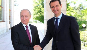 Russian President Vladimir Putin shakes hands with Syrian President Bashar Assad during their meeting in the Black Sea resort of Sochi, Russia, May 17, 2018.
