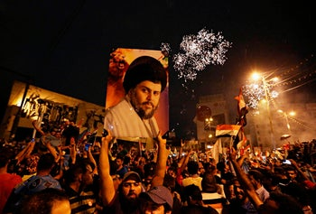 Supporters of Shiite cleric Muqtada al-Sadr carry his image as they celebrate in Tahrir Square, Baghdad, Iraq. May 14, 2018