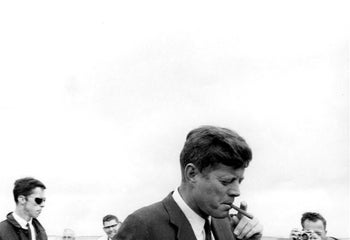 President John Kennedy arrives in Hyannis Port, Mass., puffing on a cigar May 11, 1963.