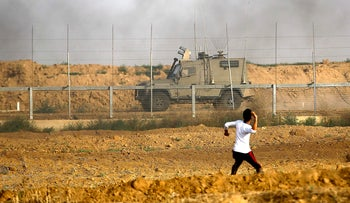 A Palestinian protester throwing stones toward Israeli forces during a protest at the Gaza border, east of Gaza City.