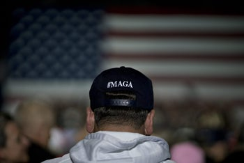 """An attendee wearing a hat reading """"#MAGA"""" listens as U.S. President Donald Trump speaks during a rally in Washington, Michigan, U.S. April 28, 2018"""