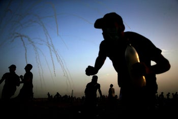Palestinians run for cover from tear gas shot by Israeli forces during a demonstration along the border between Israel and the Gaza strip. May 25, 2018