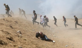 A Palestinian demonstrator reacts as others run from tear gas fired by Israeli forces during a protest marking, Israel-Gaza border, the southern Gaza Strip, May 15, 2018.