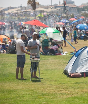 A lot of Israelis barbecue meat on Independence Day: At the Charles Clore beach in Tel Aviv. Picture shows a lot of Israelis at this seaside park, green grass, a barbecue being attended by two men, a blue & white tent and an Israeli flag.
