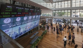 Visitors standing in front of a stock market ticker screen at the Tel Aviv Stock Exchange (TASE).