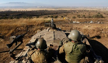 FILE PHOTO: Israeli soldiers sit atop a tank as they watch the border with Syria near the Quneitra border crossing between Israel and Syria, July 3, 2013.