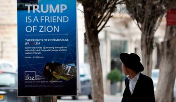 An Ultra-Orthodox Jewish man walks past a poster welcoming and supporting US President Donald Trump in downtown Jerusalem, on May 19, 2017