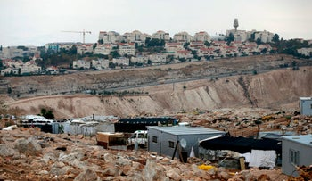 This file photo from 2017 shows a view of the Jabal al-Baba Bedouin encampment, near the Israeli settlement of Maale Adumim in the West Bank, with the settlement appearing in the background.