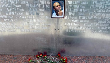 Flowers lay under a picture of the 41-year-old anti-Kremlin reporter Arkady Babchenko on the memorial wall of Moscow's journalists house in Moscow on May 30, 2018.