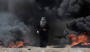 A Palestinian woman walks through black smoke from burning tires during a protest on the Gaza Strip's border with Israel, Monday, May 14, 2018. The Islamic militant group Hamas that rules Gaza, and is leading the rallies, says protests will continue until a blockade, in place since it took over Gaza in 2007, is broken. (AP Photo/Khalil Hamra)