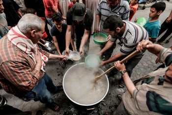 Palestinian national Waleed el-Hattab (L) cooks a soup prior to distribute it to the needy during the holy month of Ramadan, in Gaza City on May 27, 2018.