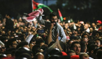 Jordanian protesters shout slogans and raise a national flag during a demonstration outside the Prime Minister's office in the capital Amman late on June 2, 2018.