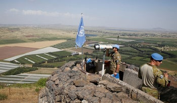 A United Nations Truce Supervision Organization military observer uses binoculars near the border with Syria in the Golan Heights.