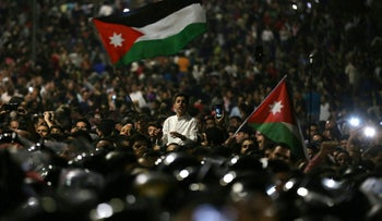 Protesters wave flags near Jordanian security forces during a demonstration outside the prime minister's office in the capital Amman late on June 3, 2018.