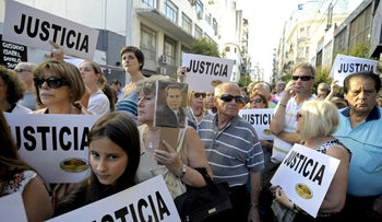 """People hold placards that read """"Justice"""" during a rally in front of the headquarters of the AMIA (Argentine Israelite Mutual Association), in Buenos Aires on January 21, 2015"""