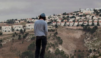 File photo: A Jewish settler looks at the West Bank urban settlement of Ma'aleh Adumim, from the E-1 area on the eastern outskirts of Jerusalem, in December 2012.