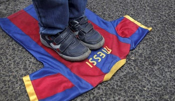 In this file photo taken on October 07, 2012, a Palestinian boy steps on a T-shirt of Spanish FC Barcelona football club with the name of it's Argentinian player, Lionel Messi, during a demonstration outside the Spanish consulate in eastern Jerusalem on October 7, 2012
