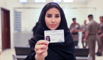 A Saudi woman displays her brand new driving license at the General Department of Traffic in Riyadh, June 4, 2018.