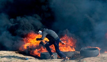 A Palestinian protester pulls a tire as smoke billows from burning tires during a demonstration along the border with the Gaza Strip east of Gaza city on June 1, 2018.