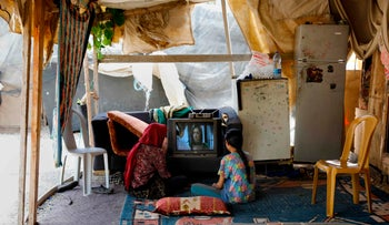 Palestinian Bedouin girls watch TV at their home in the village on May 30, 2018 in the Khan al-Ahmar Bedouin village, a village which is located between the West Bank city of Jericho and Jerusalem near the Israeli settlment of Maale Adumim and is under a demolition order.