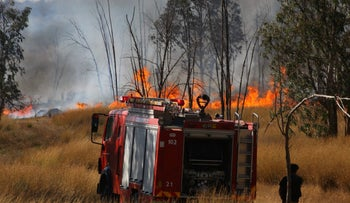 Firefighters trying to put out a forest fire caused by Palestinian incendiary kites near Kibbutz Or Haner on Monday.