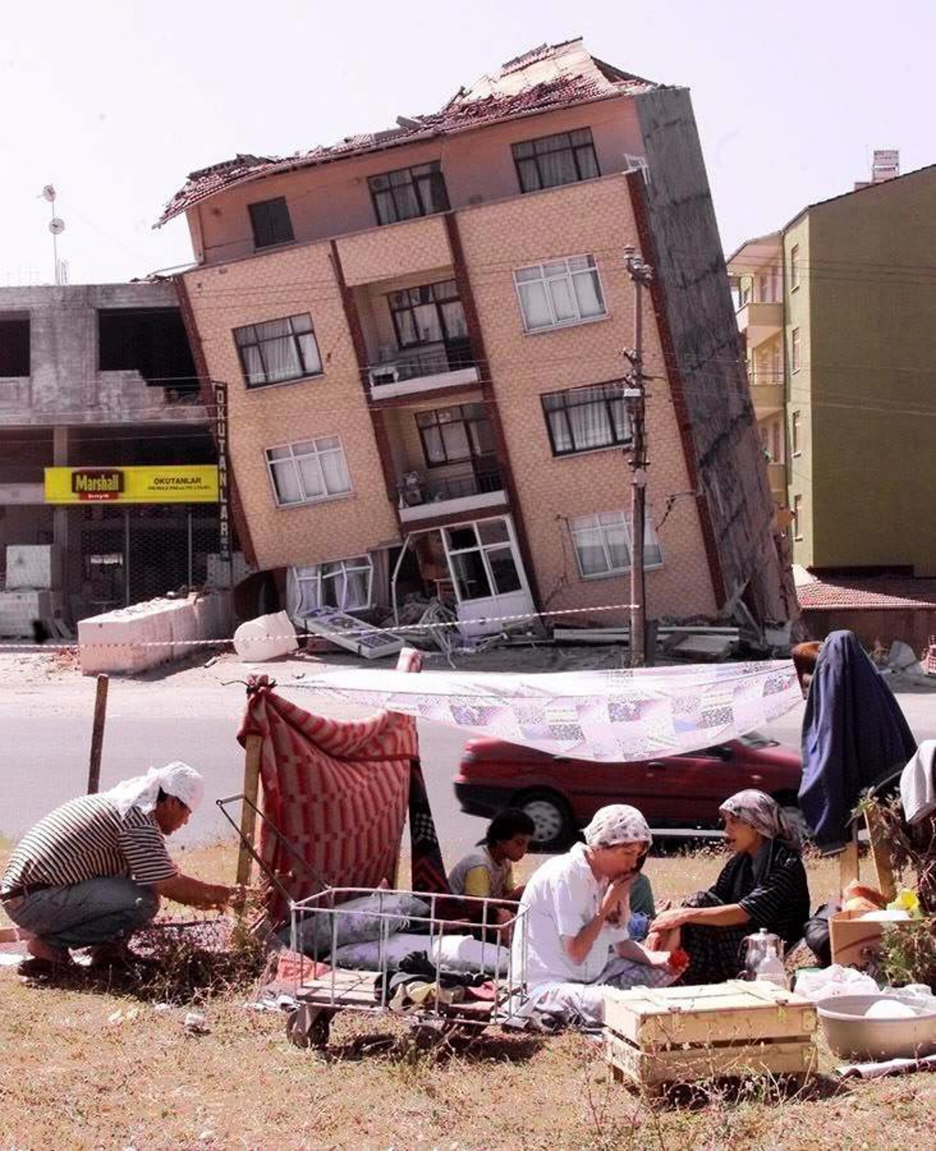A family camps in front of a wrecked house in Izmit, Aug 17, 1999: More than 2,000 people died in the 7.4 quake. More than 17,000 died in the province.