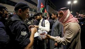 Protesters offer sweets to police officers standing guard during a protest in Amman, Jordan, early Tuesday, June 5, 2018