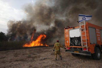 Israeli firefighters attempt to extinguish a fire caused by incendiaries tied to kites flown by Palestinian protesters from across the Gaza border. Kissufim, Israel, June 5, 2018.