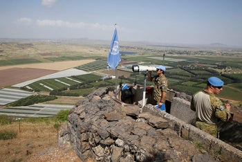 A United Nations Truce Supervision Organisation military observer uses binoculars near the border with Syria in the Israeli Golan Heights, Israel May 11, 2018