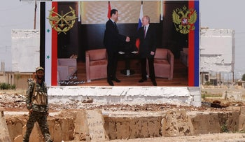 A soldier stands guard near a poster of Syria's President Bashar al Assad and his Russian counterpart Vladimir Putin during the re-opening of the road between Homs and Hama in Rastan, Syria,  June 6, 2018. REUTERS/Omar Sanadiki