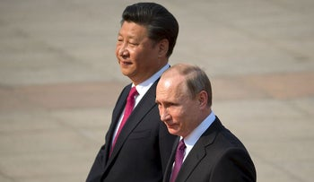 In this June 25, 2016, file photo, Chinese President Xi Jinping, left, walks with Russian President Vladimir Putin during a welcome ceremony at the Great Hall of the People in Beijing