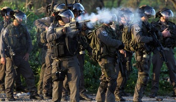 Israeli soldiers firing tear gas during clashes at the funeral of Samir Awad in the West Bank village of Budrus.