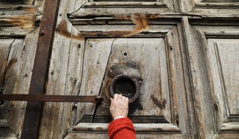 A worshipper touches the closed doors of the Church of the Holy Sepulchre in Jerusalem's Old City February 27, 2018