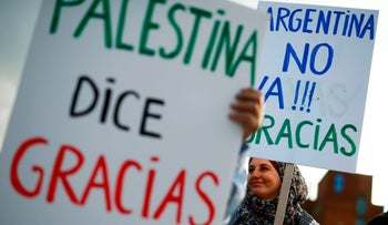 Pro-Palestinian activists holding placards reading in Spanish 'Palestine says thank you' and 'Argentina doesn't go! Thanks' on June 6, 2018.
