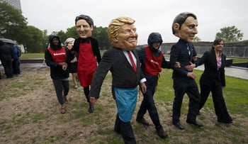 Activists wearing masks in the likeness of Justin Trudeau, Donald Trump and Emmanuel Macron during a protest ahead of the Group of Seven Leaders' summit in Canada on June 7, 2018.
