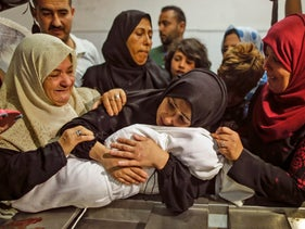 Leila al-Ghandour's mother holds her at the al-Shifa hospital in Gaza City, May 15, 2018.