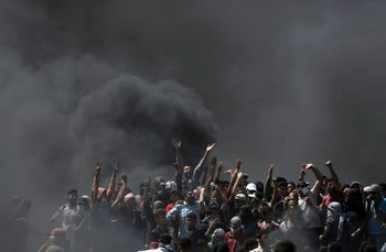 Palestinian protesters chant slogans as they burn tires during a protest on the Gaza Strip's border with Israel, May 14, 2018.