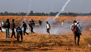 Palestinian demonstrators throwing back tear gas canisters across the border into Israel during a demonstration east of Khan Yunis on June 5, 2018.