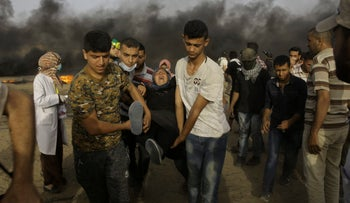 Palestinian protesters evacuate a wounded youth near the Gaza Strip's border with Israel, east of Khan Younis,  May 25, 2018.