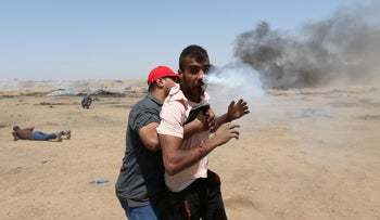 A wounded Palestinian demonstrator reacts as he is hit in the face with a tear gas canister fired by Israeli troops during a protest marking al-Quds Day, (Jerusalem Day), at the Israel-Gaza border in the southern Gaza Strip June 8, 2018. REUTERS/Ibraheem Abu Mustafa
