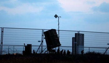 Israeli soldiers walk next to an Iron Dome anti-missile system positioned near the city of Ashkelon, Israel May 29, 2018.
