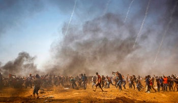 Palestinian protesters take cover from tear gas during a demonstration along the border with Israel in the central Gaza Strip on June 8, 2018.