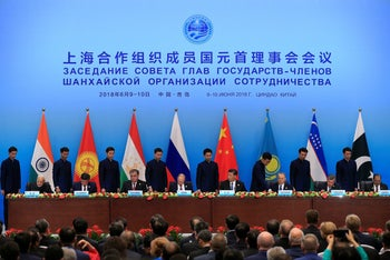 India's Prime Minister Narendra Modi, Kyrgyzstan's President Sooronbay Jeenbekov, Tajikistan's President Emomali Rahmon, Russia's President Vladimir Putin, China's President Xi Jinping, Kazakhstan's President Nursultan Nazarbayev, Uzbekistan's President Shavkat Mirziyoyev and Pakistan's President Mamnoon Hussain attend a signing ceremony during Shanghai Cooperation Organization (SCO) summit in Qingdao, Shandong Province, China June 10, 2018.