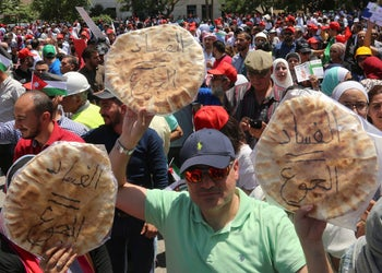 """Jordanian protesters shout """"bread"""" in front of the Labour Union offices in Amman, Jordan Wednesday, June 6, 2018. """"Corruption equals hunger,"""" is written in Arabic on loaves of bread."""