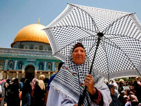 A woman stands before the Dome of the Rock holding an umbrella adorned with Palestinian keffiyeh patterns, during the last Friday prayers of the Muslim holy month of Ramadan. Jerusalem, June 8, 2018