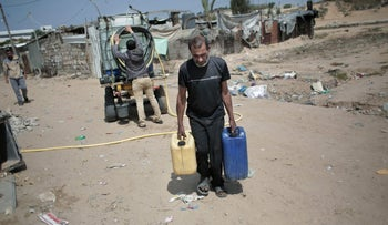A Palestinian man carries plastic gallons he filled with drinking water from a vendor in Khan Younis refugee camp, southern Gaza Strip, April 16, 2016